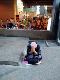 An elderly woman bows her head, waiting for charity.
