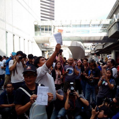 Youth activist leader Sirawit Serithiwat waves the mock ballot sheet to activists on the BTS Station.