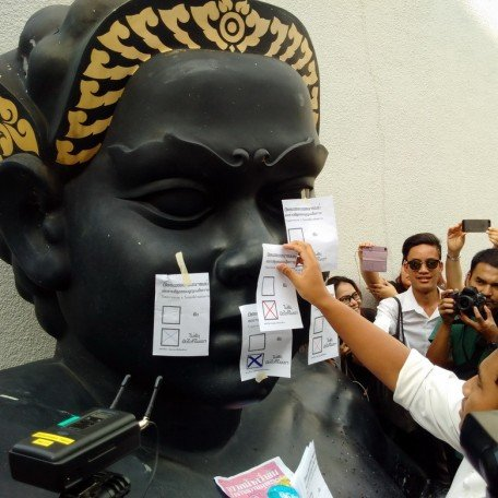 A Thai activist sticks mock ballots on a statue, displaying his opposition to the junta-endorsed draft constitution.