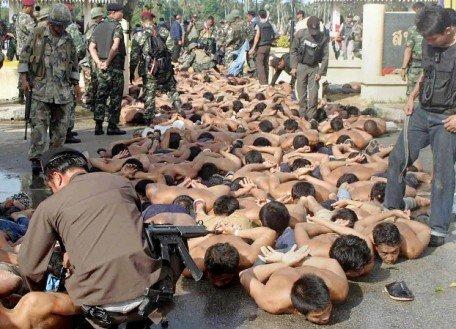 Demonstrators lie on the pavement after their arrest oustide Tak Bai police station in Narathiwat province, Thailand, Oct. 25, 2004. [AFP]