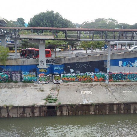 Art, almost hidden from plain sight; sandwiched by walls and a polluted river.