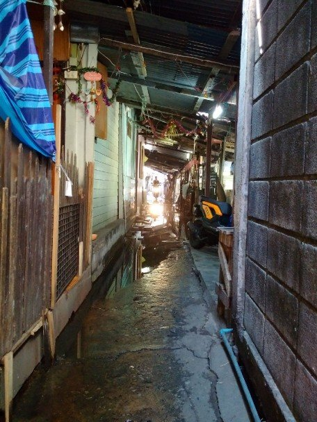 A narrow wet path, leading deeper into a slum in Bangkok.
