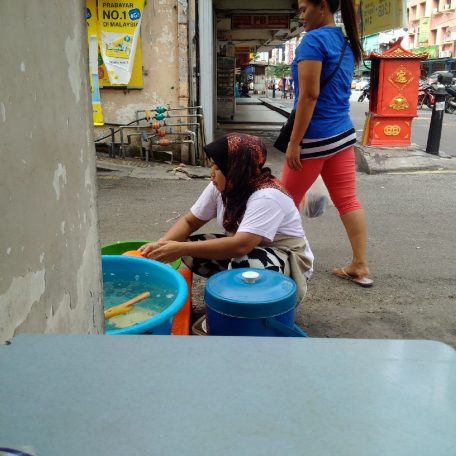 A migrant from Indonesia washes dirty dishes at a street food stall.