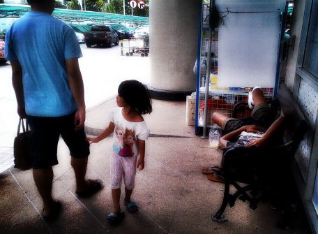 A child begs for coins as her sick father rests on a bench. Homeless in Bangkok